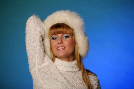 beautiful blond woman in a fur cap on a blue background Stock Photo - 21805255
