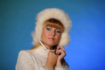 beautiful blond woman in a fur cap on a blue background Stock Photo - 21805256