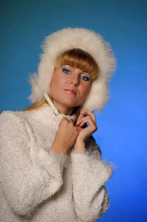 beautiful blond woman in a fur cap on a blue background Stock Photo - 21805257