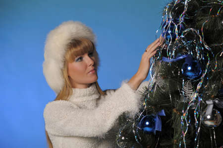 Beautiful blonde in fur hat and Christmas tree photo