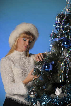 Beautiful blonde in fur hat and Christmas tree Stock Photo - 21805262