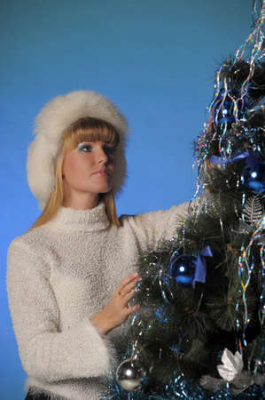 Beautiful blonde in fur hat and Christmas tree Stock Photo - 21805264