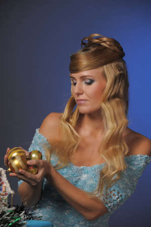 blonde with beautiful hairstyle and christmas balls in his hands photo