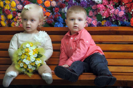 conversating: Children on a bench with flowers in the background
