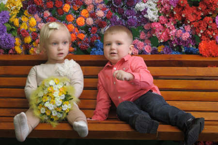 Children on a bench with flowers in the background Stock Photo - 21741987