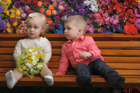 Children on a bench with flowers in the background Stock Photo - 21742003