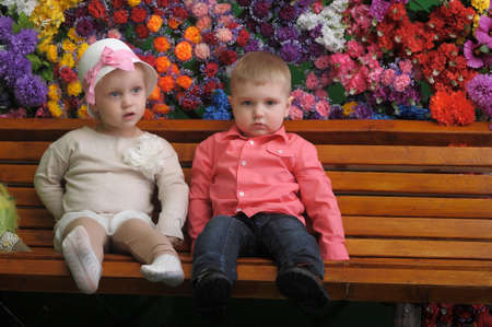 Children on a bench with flowers in the background Stock Photo - 21741706