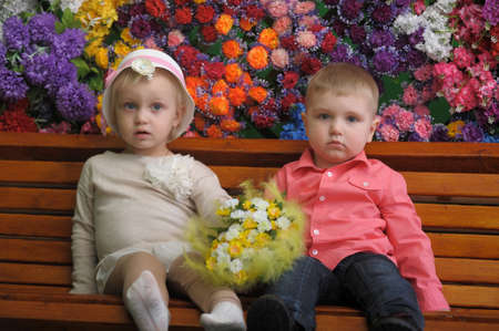 Children on a bench with flowers in the background Stock Photo - 21741726