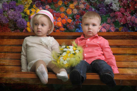Children on a bench with flowers in the background photo