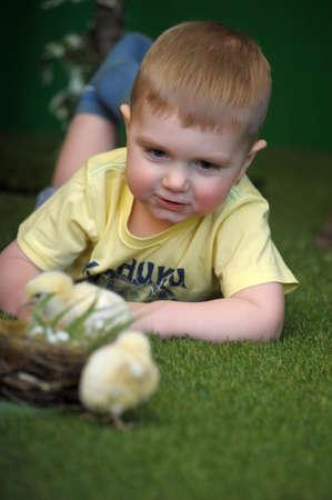 Happy boy on floor with pet chick photo