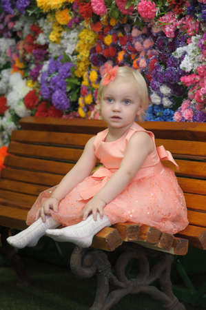 year-old girl on a bench with flowers photo