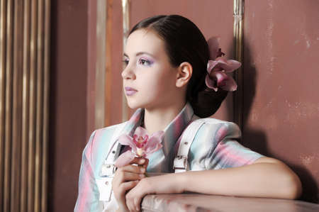 girl with beautiful hairstyle with orchid in her hair photo