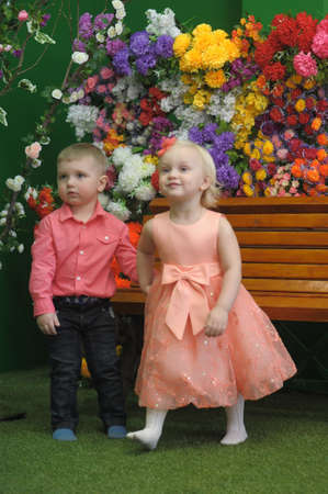 girl and boy children near the bench and floral background photo