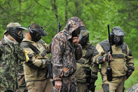 outside shooting: a group of players in a paintball Editorial