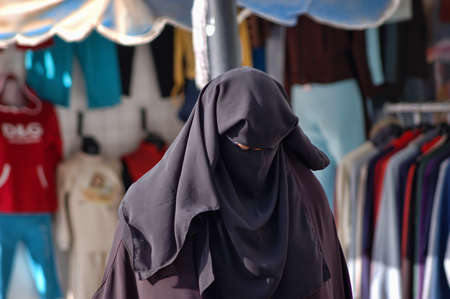 niqab: woman in a burqa on the streets of Egypt