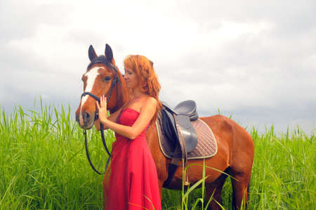 beautiful woman in a red dress with a horse photo
