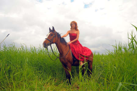 young beautiful woman in a red dress on a horse photo