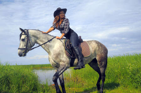 girl in a cowboy hat on a horse photo