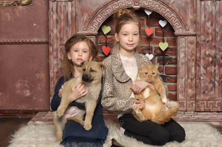 two girls with a cat and a puppy in her arms photo