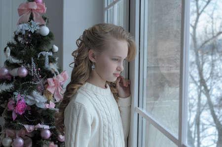chica en la ventana de la Navidad