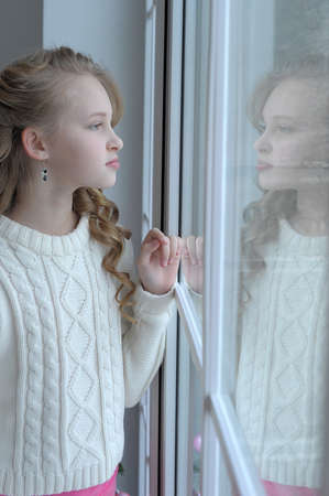 Teen girl at the window in winter photo