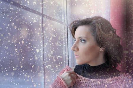 Mujer joven detrás de la ventana la nieve