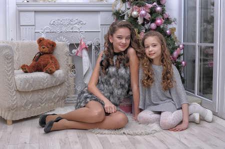 dos hermanas cerca de un árbol de Navidad