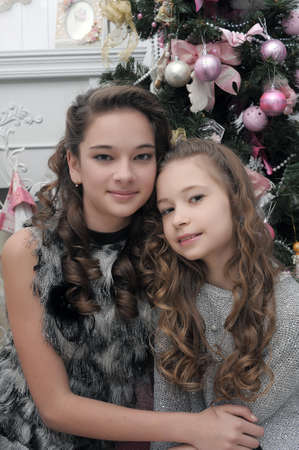 two sisters near a Christmas tree Stock Photo - 22160610