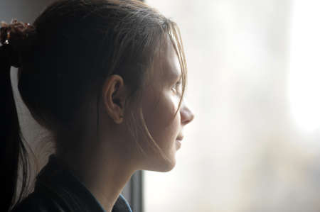 contemplative: teen girl looking out the window Stock Photo