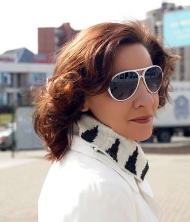 Portrait of a young woman in a white coat and sun glasses on the street photo