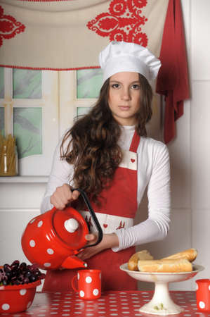 stand teapot: Girl in the kitchen with an apron and a cup of tea. Stock Photo