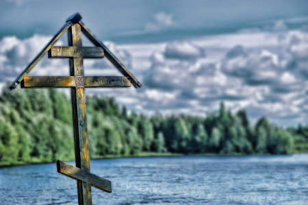 Wooden cross on the shores of Lake. photo