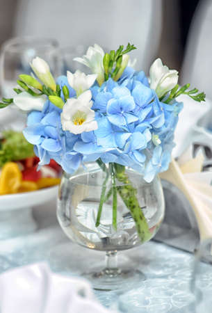 Soft white and blue flowers in a glass. photo