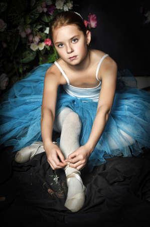 a young ballerina in a blue skirt on a floral background tying pointe shoes photo