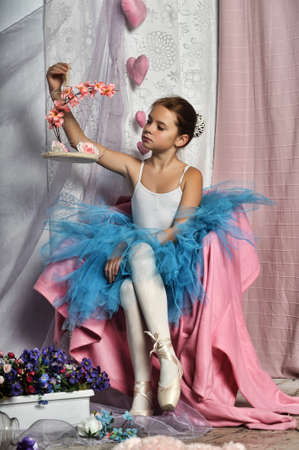 young ballerina in a blue skirt on a floral background photo