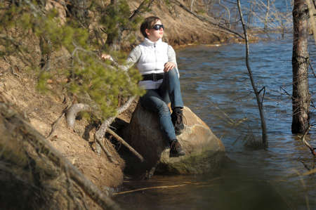 girl sitting on a rock near the water photo