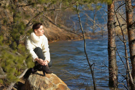 lazybones: girl sitting on a rock near the water Stock Photo