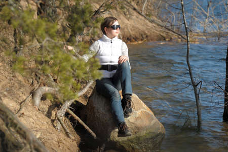 lazybones: teen girl sitting on a rock near the water