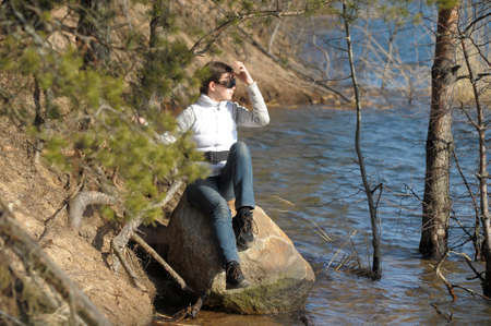 teen girl sitting on a rock near the water photo