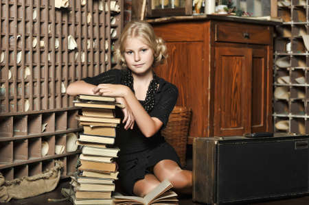 Teen girl dressed in retro style with a stack of books  photo