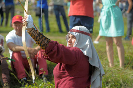 woman in medieval clothes archery