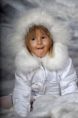 Little girl in white winter coat and hat  photo
