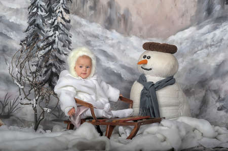 Girl on a sled next to a snowman  photo
