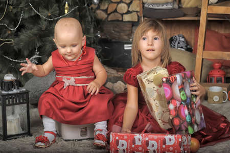 Two little girls with red dresses and Christmas decorations photo