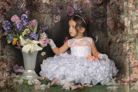 Funny girl hamming in white dress with flowers in a vase photo