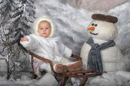 Girl on a sled next to a snowman. photo