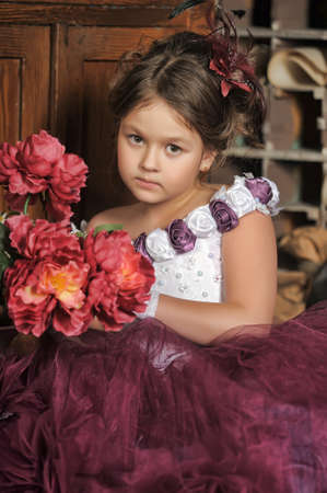 Vintage portrait of little girl in purple dress hold flowers photo