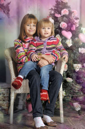 Smiling sisters under the tree with gifts  photo