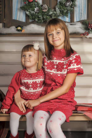 Sisters on Christmas time siting under house in studio  photo