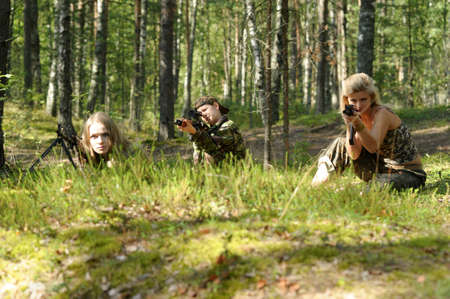 a group of armed women in the woods photo